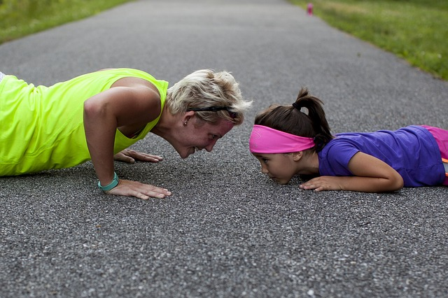 woman and child doing pushups together