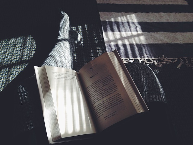 person relaxing with a book on the floor