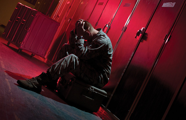stressed soldier with head in hands by Flickr user Justin Connaher