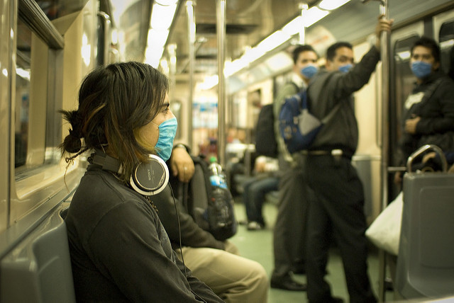 people on subway wearing medical masks by Flickr user Eneas De Troya