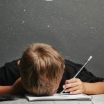 Boy holding pencil with his head down on desk