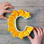 Hands adjusting a letter C made out of orange slices