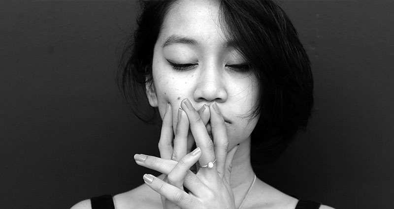 Stressed woman with hands near mouth