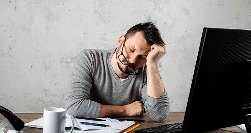 Tired man at desk with computer