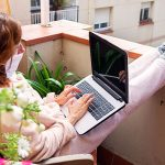 Red haired woman in face mask and pajamas using laptop on balcony