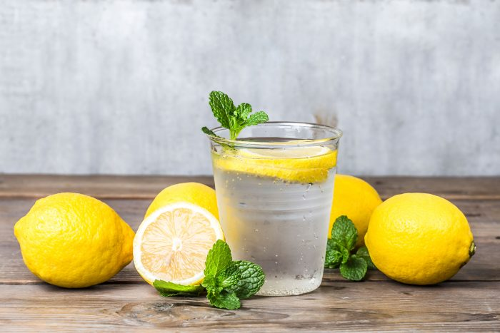 Clear glass of water with lemon slices in it