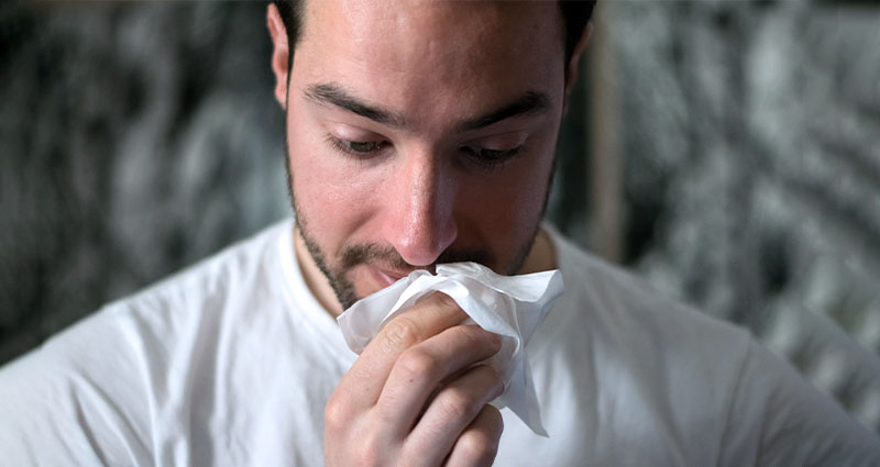 Man holding tissue to nose