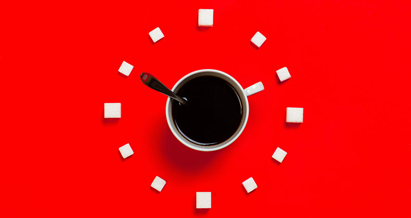 image of coffee cup surrounded by sugar cubes