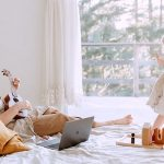 mom playing guitar on bed while kid dances