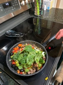 Meat and vegetables cooking in skillet